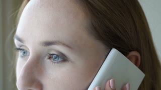 Pretty girl with beautiful blue eyes talking on cellphone, steadycam shot