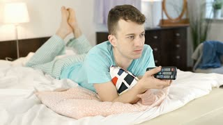 Relaxed man lying in bed and watching television, steadycam shot