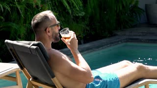 Relaxed man lying on sunbed and drinking beverage, steadycam shot, slow motion s