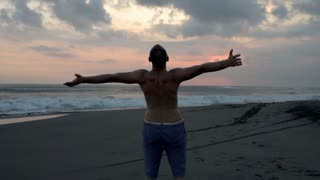 Relaxed man standing on the sandy beach, steadycam shot, slow motion shot at 240