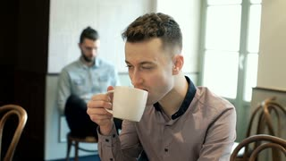 Skinny man drinking coffee in the cafe and smiling to the camera, steadycam shot
