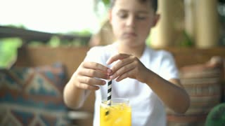 Small child sitting in the outdoor cafe and drinking fresh lemonade, steadycam s