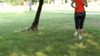 Sporty girl answers cellphone while running in the park, steadycam shot
