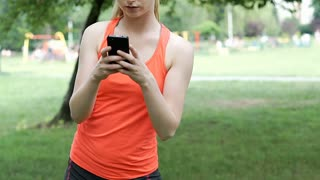 Sporty girl doing warm-up in the park and texting on smartphone, steadycam shot