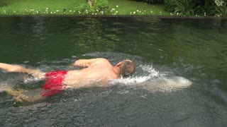 Sporty man swimming in the pool, steadycam shot, slow motion shot at 240fps