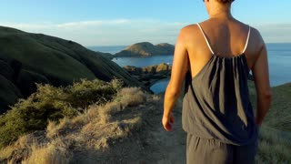 Sporty woman walking on the mountain, slow motion shot at 240fps, steadycam shot
