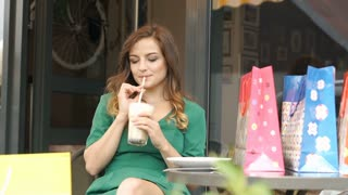 Stylish brunette relaxing in the outdoor cafe and drinking frappe, steadycam sho