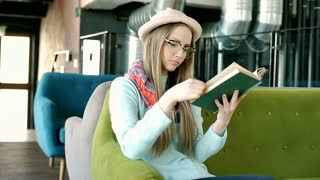 Stylish girl in bowler hat looks happy while reading book in the cafe