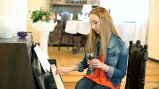 Thoughtful girl playing piano and drinking red wine