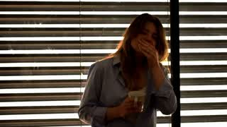 Tired woman yawning in the dark room and holding cup of coffee