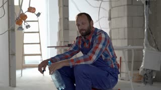 Tired worker sitting during his break and drinking water, steadycam shot