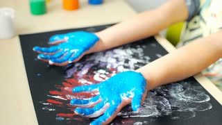 Toddler holding his dirty hands from paint while sitting by the table