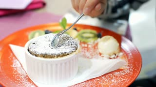 View of female's hands holding spoon and eating cake, steadycam shot