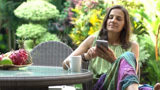 Woman answers cellphone and receives good news while sitting in exotic garden, s
