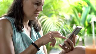 Woman browsing internet on smartphone and looks worried, close up, steadycam sho