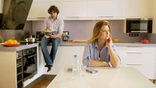 Woman having tootache and taking painkiller while sitting in the kitchen