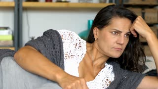 Woman in cosy clothes lying on the sofa and thinking about something