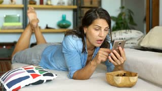 Woman in denim shirt looks shocked while checking something on smartphone