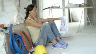 Woman looks tired and throwing papers while sitting in her new apartment, steady