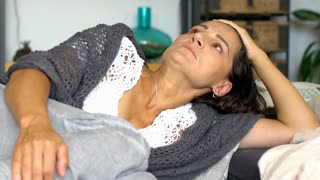 Woman looks worried while lying on the sofa alone