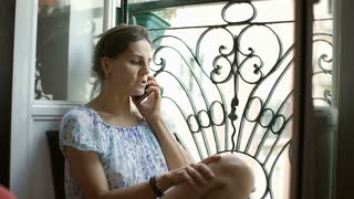 Woman receives bad news while speaking on cellphone next to the bars