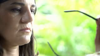 Woman relaxing in exotic place and cleaning sunglasses, close up, steadycam shot