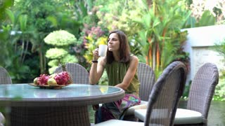 Woman relaxing in the garden and drinking coffee, steadycam shot