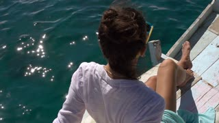 Woman relaxing on the yacht and enjoying the sun, close up, slow motion shot at 240fps, steadycam shot