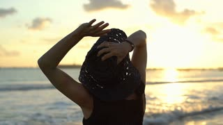Woman standing back on the beach and looking on sunset, steadycam shot
