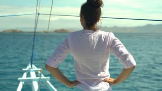 Woman standing back on the boat and feels free, steadycam shot