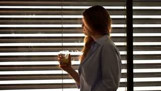 Woman standing next to the window and drinking water, steadycam shot