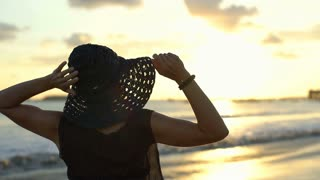 Woman standing with her hands up and admires the sunset, steadycam shot