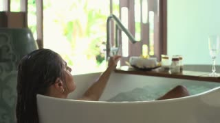 Woman taing towel and dries her face during bath, steadycam shot, slow motion sh