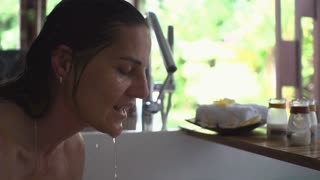 Woman throwing water on her face, steadycam shot, slow motion shot