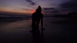 Woman walking on her knees on the sandy beach, slow motion shot at 240fps, stead