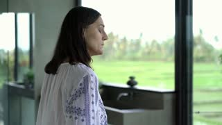 Woman walking to the window and looks irritated, steadycam shot