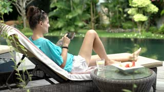 Woman watching video on smartphone and drinking water while relaxing next to the