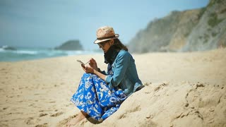 Woman wearing protection from sun and browsing internet on smartphone by using s