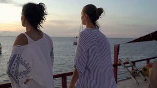 Women admires the view and looking on boats, steadycam shot, slow motion shot at
