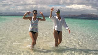 Women walking in the clear sea and waving to the camera, steadycam shot, slow mo