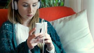 Worried girl listening music on headphones and checking smartphone, steadycam sh