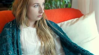 Worried girl wrapped up in blanket doing sad look to the camera, steadycam shot