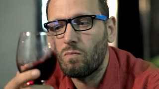 Worried man looking to the camera and drinking red wine, steadycam shot