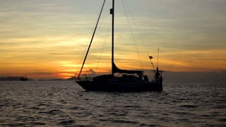 Yacht floating on the sea while sunsetting, slow motion shot at 240fps, steadyca
