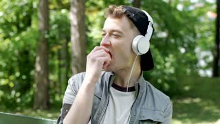 Young man eating an apple in the park and listening music on headphones, steadyc