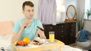 Young man eating breakfast in bed and watching television, steadycam shot
