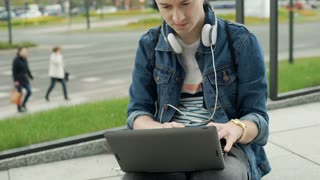 Young man listening music and using laptop in the city, steadycam shot