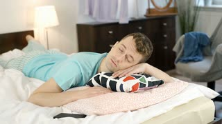 Young man looks irritated after being bothered by message during sleep, steadyca