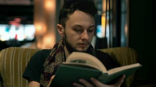 Young man turning pages in the book while looking for something