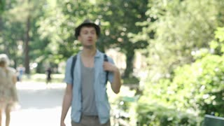 Young man walking with backpack in the park and looking for the way, steadycam s
